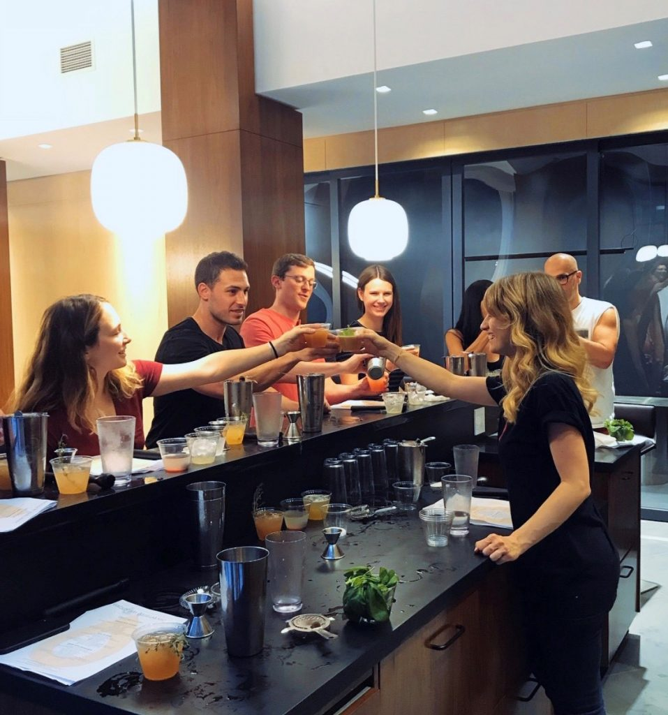 group at the bar making cocktails